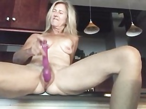 Naked blonde stretches out her gams petting muff with a massive fake penis